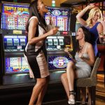 Group of Women Celebrating in Front of Slot Machines
